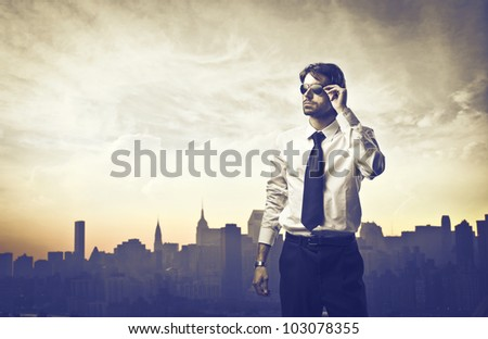 Portrait of a young businessman with skyline of a big city in the background - stock photo