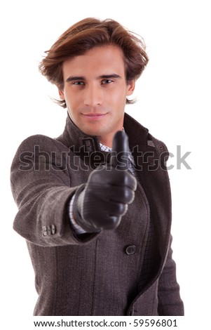 Portrait of a young businessman with thumb up, in autumn/winter clothes, isolated on white. Studio shot - stock photo