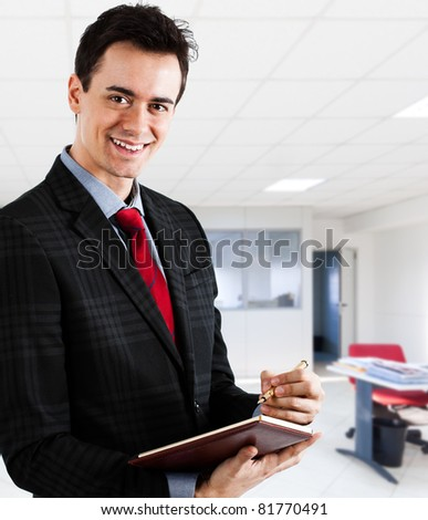 Portrait of a young businessman writing something on a notebook in his office - stock photo