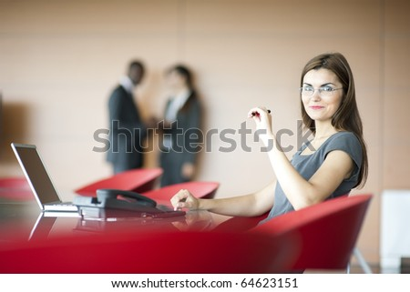 Portrait of a young businesswoman, colleagues on backgrounds - stock photo