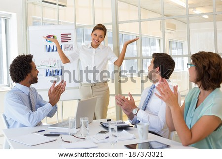 Portrait of a young businesswoman giving presentation to colleagues in a bright office - stock photo