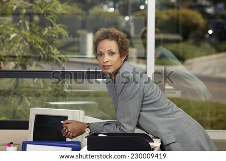 Portrait of a young businesswoman leaning over a desk