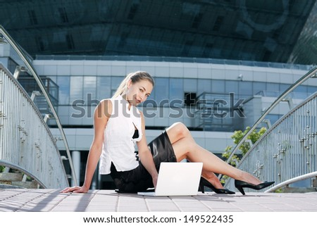 Portrait of a young businesswoman  near classic office buildings in a city with laptop - stock photo