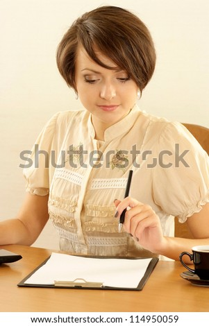 portrait of a young businesswoman on a beige - stock photo