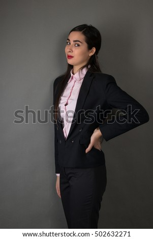 Portrait of a young businesswoman on gray background.
