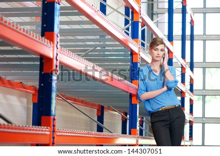 Portrait of a young businesswoman on mobile phone in warehouse - stock photo