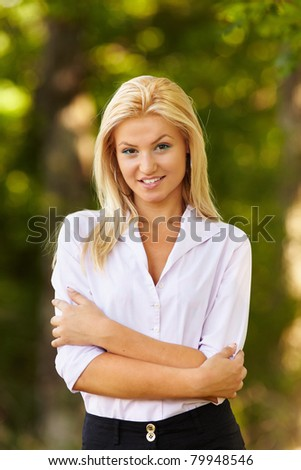 Portrait of a young businesswoman outdoor with her arms folded - stock photo