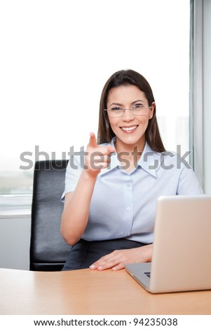 Portrait Of A Young Businesswoman Pointing At The Viewer In Her Office. - stock photo