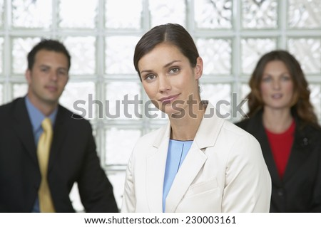 Portrait of a young businesswoman posing for the camera with colleagues in the foreground - stock photo