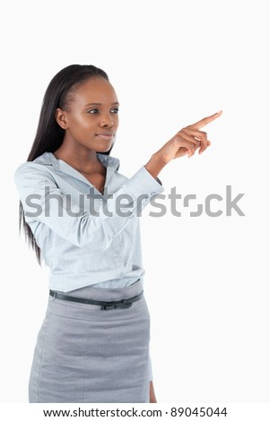Portrait of a young businesswoman pressing an invisible key against a white background