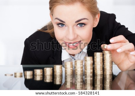 Portrait Of A Young Businesswoman Stacking Coins On Desk - stock photo