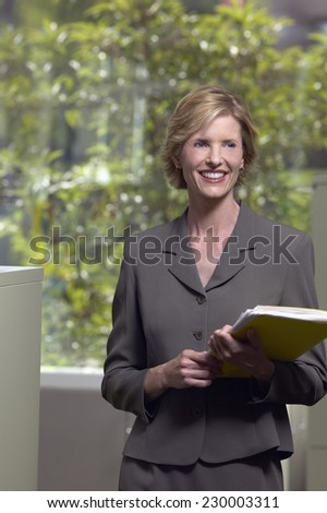 Portrait of a young businesswoman standing by the water cooler holding a folder - stock photo