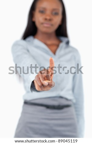 Portrait of a young businesswoman touching an invisible screen against a white background - stock photo