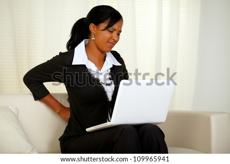 Portrait of a young businesswoman with back pain that is working on laptop at home indoor - stock photo