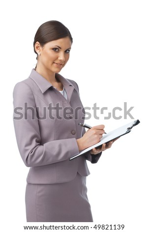 Portrait of a young businesswoman writing something in her folder and smiling - stock photo