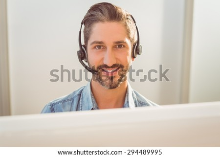 Portrait of a young call centre representative using headset in office - stock photo