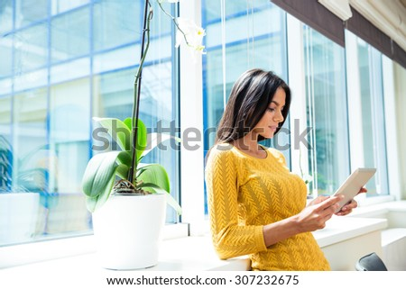 Portrait of a young casual businesswoman using tablet computer in office near window - stock photo