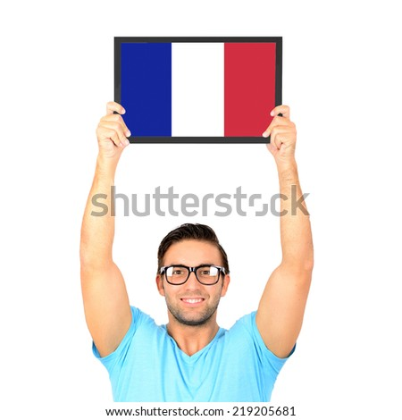 Portrait of a young casual man holding up board with National flag of France - stock photo