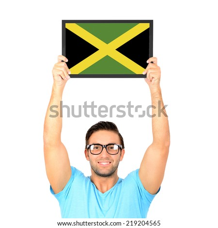 Portrait of a young casual man holding up board with National flag of Jamaica - stock photo