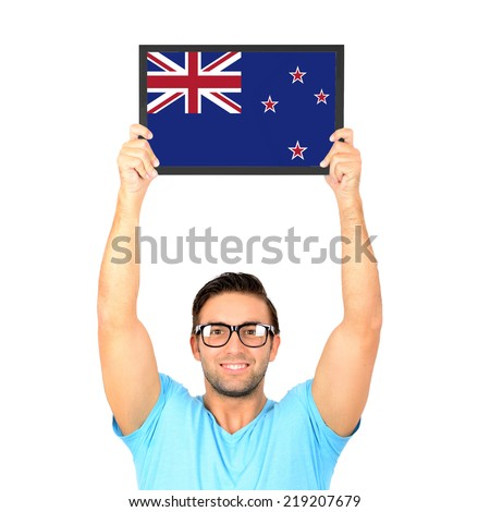 Portrait of a young casual man holding up board with National flag of New Zealand