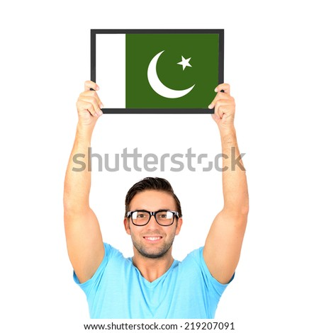 Portrait of a young casual man holding up board with National flag of Pakistan - stock photo