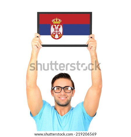 Portrait of a young casual man holding up board with National flag of Serbia - stock photo