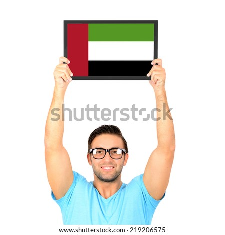 Portrait of a young casual man holding up board with National flag of United Arab Emirates - stock photo