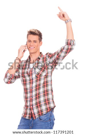 portrait of a young casual man winning while speaking on the phone and pointing up, isolated on white