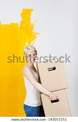 Portrait of a young casual woman carrying cardboard boxes in front of half yellow painted wall - stock photo