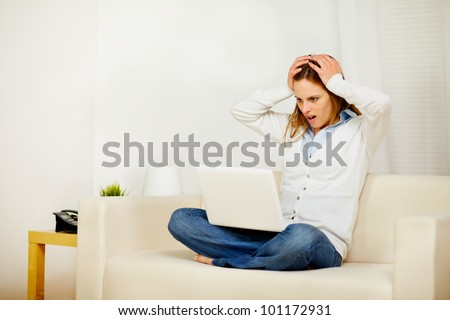 Portrait of a young casual woman working on sofa with the hands on the head