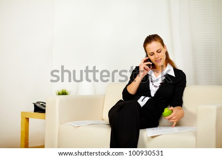 Portrait of a young caucasian business woman working with documents while is eating a green apple and speaking on the phone