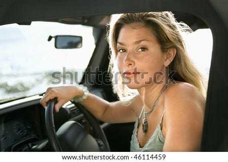 Portrait of a young Caucasian female sitting in the driver's seat of an SUV and looking at the camera, with ocean waves visible in the background. Horizontal format. - stock photo