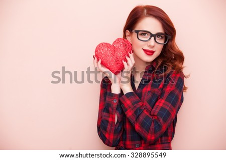 Portrait of a young caucasian girl with gift on pink background. - stock photo