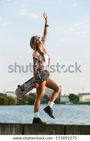 Portrait of a young caucasian skater woman during the sunset, outdoor - stock photo