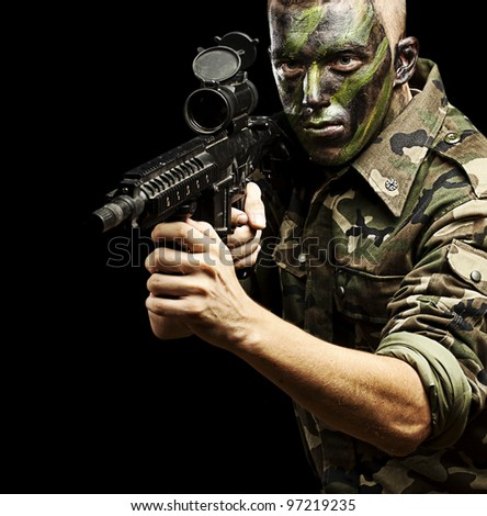 portrait of a young caucasian soldier with a jungle camouflage over a black background - stock photo