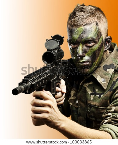 portrait of a young caucasian soldier with a jungle camouflage over an orange background - stock photo