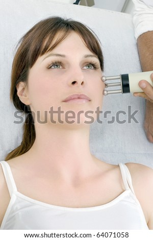 portrait of a young caucasian woman receiving electrostimulation lifting - stock photo