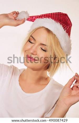 Portrait of a young Caucasian woman wearing white t-shirt and red Santa's hat. Christmas holiday concept. Studio shot on white background.