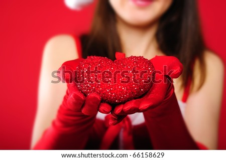 Portrait of a young charming girl dressed as Santa's gift in the form of heart in his hands. Happy New Year!
