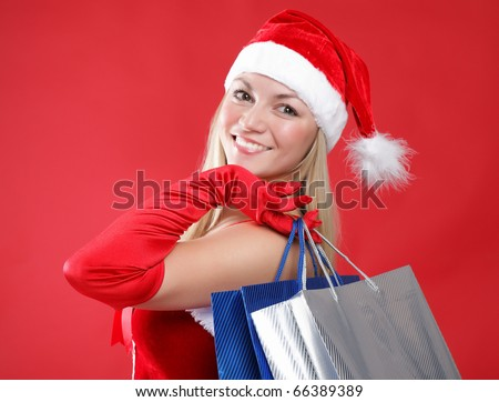 Portrait of a young charming girl dressed as Santa with a bag of shopping in their hands