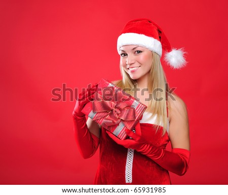 Portrait of a young charming girl dressed as Santa with a gift in their hands. Happy New Year! - stock photo