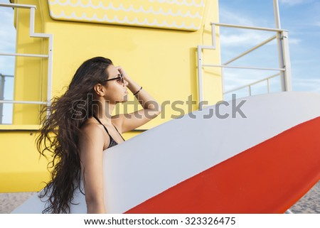 Portrait of a young charming surfer female enjoying sun and free time after her surfing in a beautiful summer day, attractive Latin women hold copy space area surfing board while standing on the beach - stock photo