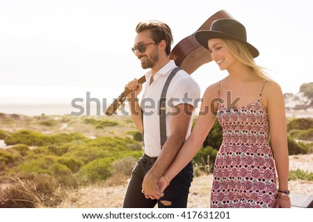 Portrait of a young cheerful couple walking holding hands. Boyfriend walking with his girlfriend and holding a guitar. Lovers going to the beach. - stock photo