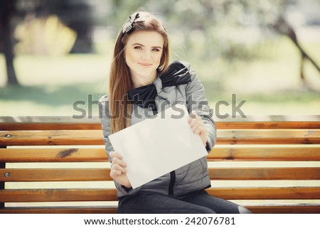 Portrait of a young cheerful girl of European appearance, which is holding a blank white banner outdoor city park - stock photo