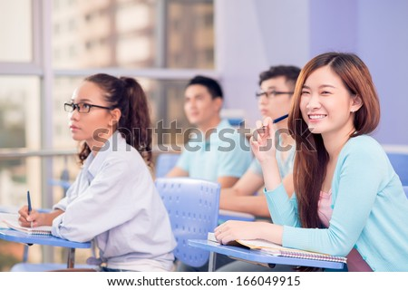 Portrait of a young cheerful student smiling and looking at camera on the foreground - stock photo