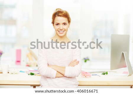 Portrait of a young cheerful woman in her office - stock photo