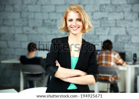 Portrait of a young cheerful woman standing with arms folded in office - stock photo