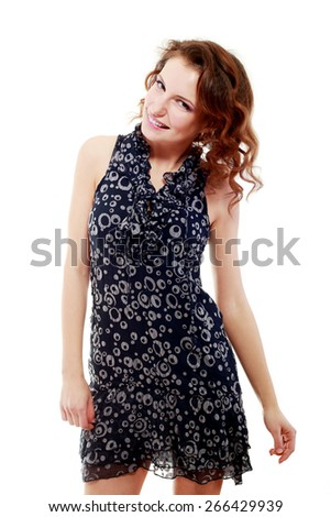 Portrait of a young cheerful young woman in gray dress posing - stock photo