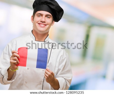 Portrait Of A Young Chef Holding French Flag, indoor