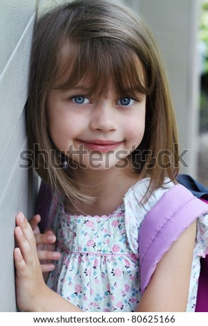 Portrait of a young child carrying a book bag or back pack. - stock photo